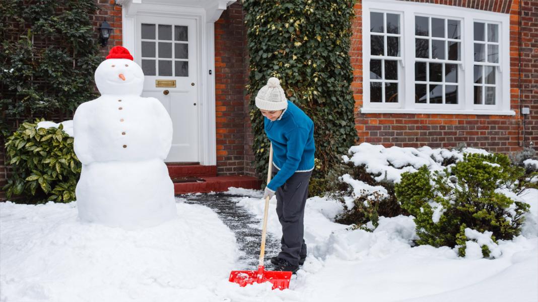 Kind beim Schnee räumen
